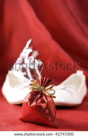 Christmas decoration (Red christmas sack, little princess slippers and crown) on a red silk background - stock photo