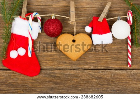 Christmas decoration - red sock gift, gingerbread heart, globes, candy cane, rope with wood hooks and fir branches on old wooden background - stock photo