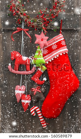 christmas decoration santa's sock and handmade toys over rustic wooden background. nostalgic retro style picture with falling snow effect - stock photo