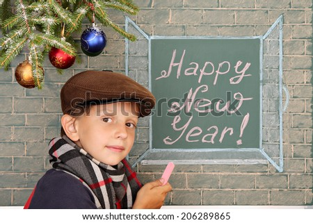 Christmas decoration, schoolboy and message on chalkboard: Happy New Year! - stock photo