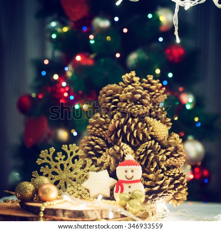 Christmas decoration. Snowman cookie, pinecone, lights, Christmas tree in background. Shallow depth of field. - stock photo