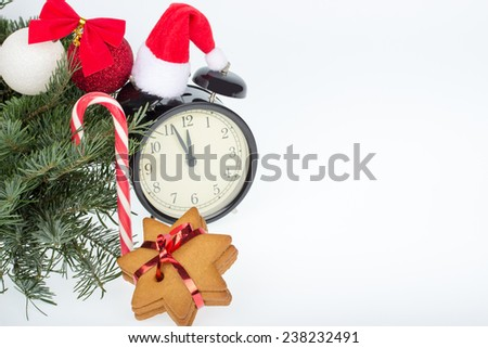 Christmas decoration - table clock, gingerbread, candy cane, balls and fir branches on a white background - stock photo