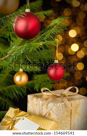 Christmas decoration tree, baubles and gifts on shining lights background - stock photo