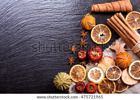 christmas decoration: various dried fruit, cinnamon sticks and anise stars on dark background