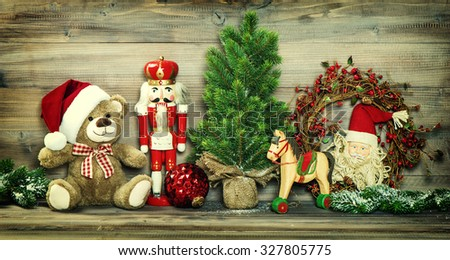 Christmas decoration. Vintage toys Teddy Bear, rocking horse and Nutcracker. No name mass production ware. Retro style toned photo with vignette - stock photo