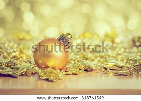 Christmas decoration with bauble ball on wooden table over lights background, selective focus, rustic style