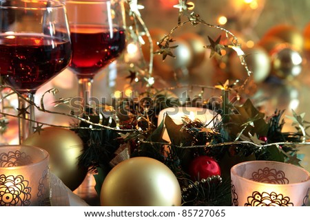 Christmas decoration with baubles,candle lights,green twig and red wine in glasses on golden background with twinkle lights. - stock photo
