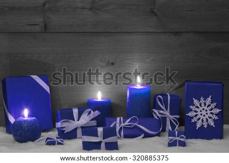 Christmas Decoration With Blue Candles, Handmade Christmas Gifts, Presents, Snowflake, Snow. Peaceful Atmosphere With Candlelight. Wooden,Vintage,Rustic Background.Copy Space. Black And White Image - stock photo