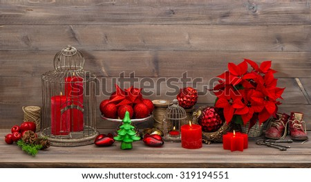 Christmas decoration with burning candles, antique baby shoes, red flower poinsettia, stars and baubles. Retro style toned picture - stock photo
