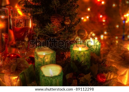Christmas decoration with candle, baubles, christmas tree, glass of champagne and twinkle lights on background.
