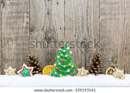 christmas decoration with colorful gingerbread cookies and cones on old wooden board - stock photo