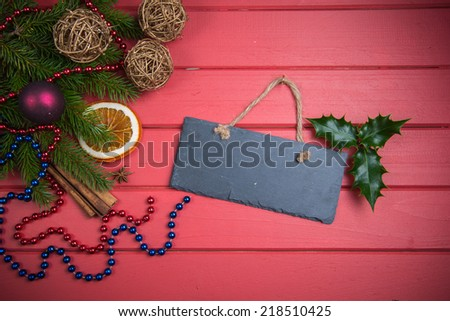 Christmas decoration with copy space on stone slate and red wooden background