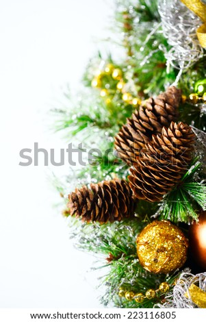 Christmas decoration with fir branches, golden and silver baubles and cones. Vertical composition over white background, space for your text. - stock photo