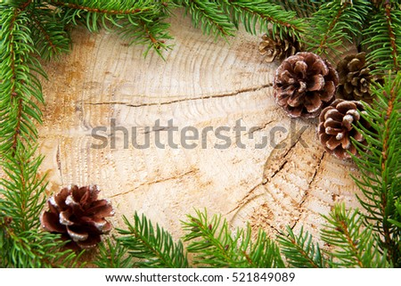 Christmas decoration with fir cones and green branch frame, top view with copy space on wood. Christmas card.