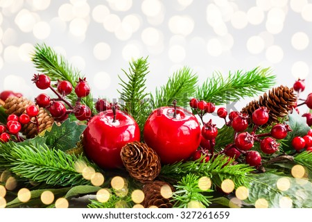 Christmas decoration with fir tree, pine cones, red apples and holly berries - stock photo