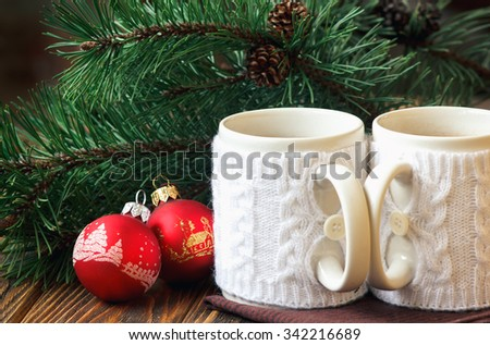 Christmas Decoration with fir twigs, red balls and cups of hot chocolate dressed in knitted warm winter mug holder on wooden background - stock photo