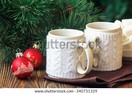 Christmas Decoration with fir twigs, red balls, marshmallow and cups of hot chocolate dressed in knitted warm winter mug holder on wooden background - stock photo