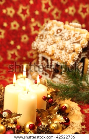 Christmas decoration with four candles and gingerbread house on red Christmas background. Shallow DOF, copy space - stock photo