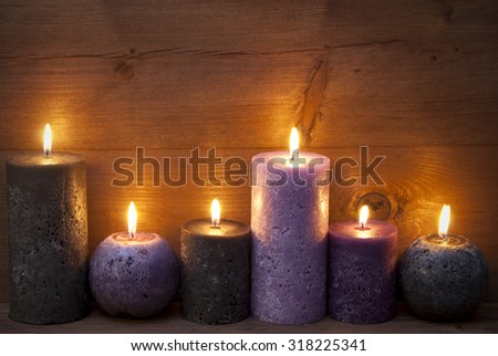 Christmas Decoration With Light Purple, Lavender And Black Candles. Peaceful, Romantic Atmosphere With Candlelight. Wooden Background For Copy Space. Vintage Rustic Style - stock photo