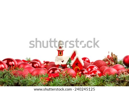 Christmas decoration with many scattered red round ornaments for Christmas tree with toy house in middle.Holiday decorations isolated on white background. Empty or copy space for holiday greeting card - stock photo