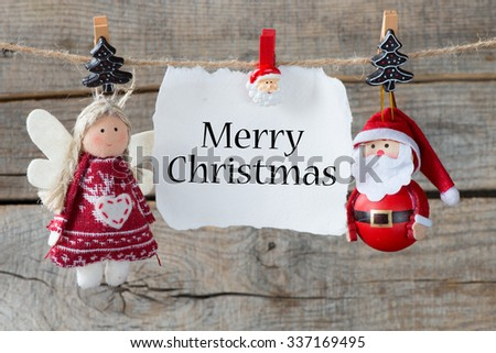 Christmas decoration with merry christmas on paper sheet over wooden background - stock photo