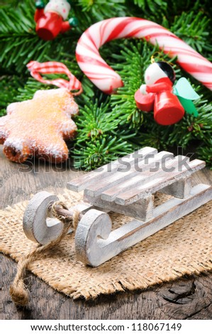 Christmas decoration with mini sleigh on wooden background - stock photo