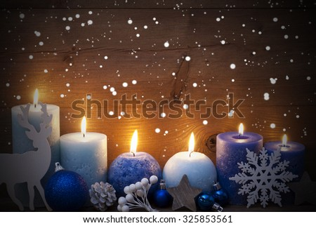 Christmas Decoration With Purple And Blue Candles,Reindeer, Christmas Ball, Snowflakes, Fir Cone,Star. Peaceful Atmosphere With Candlelight. Wooden Background For Copy Space. Vintage Style - stock photo