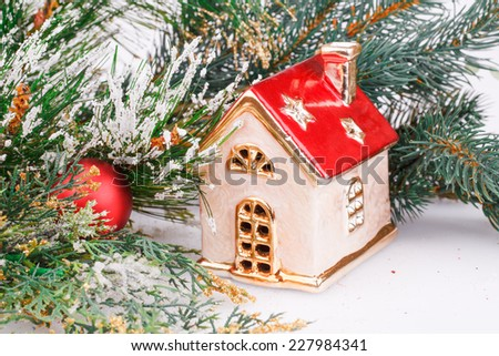 Christmas decoration with red ball, fir-tree branch and toy house. - stock photo