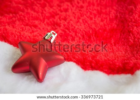 Christmas decoration with red bauble ball on Santa Claus hat background
