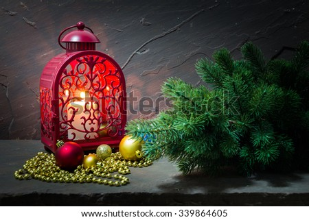 Christmas decoration with red lantern, bauble and fir on brown stone table over stone grunge background - stock photo