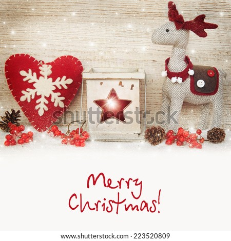 Christmas decoration with reindeer, lantern on wooden background for a greeting card.