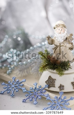 Christmas decoration with santa claus figurine and blue snowflakes.  - stock photo