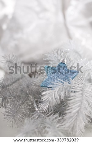 Christmas decoration with silver twig and blue star bauble.  - stock photo