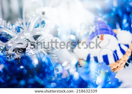 Christmas decoration with smiling snowman. Abstract blue holiday decorations: baubles, stars, tinsel and garland. Blurred image with selective focus toned in vintage colors. Very good for your text. - stock photo