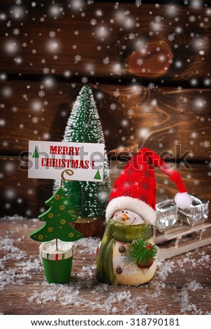 christmas  decoration with snowman figurine and christmas tree shaped greeting card holder with wishes on wooden background - stock photo