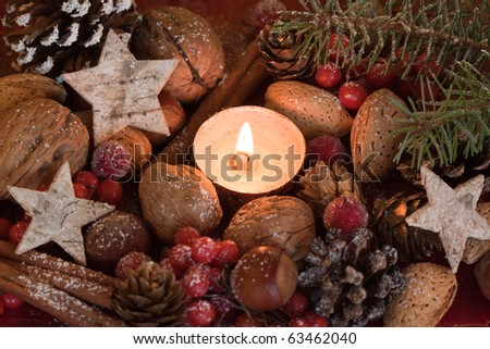 Christmas decoration with stars, hazelnuts, cinnamon and candle. - stock photo