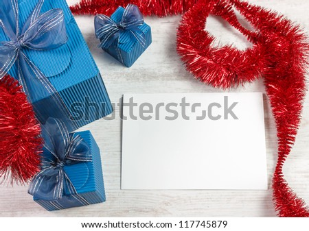 Christmas decoration with three blue gift boxes and red garland against wooden white table. White paper with copy space for your best wishes. - stock photo