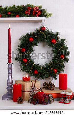 Christmas decoration with wreath, candles and present boxes on shelf on white wall background - stock photo