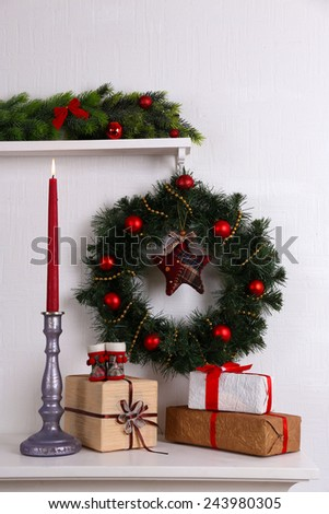 Christmas decoration with wreath on shelf on white wall background - stock photo