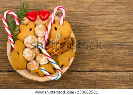 Christmas decoration - wooden bowl with gingerbread, candy cane, red hearts, cinnamon and fir branch on old wooden background - stock photo