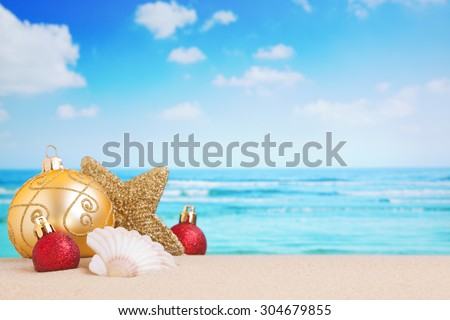 Christmas decorations and baubles in the sand on a beach on a bright and sunny day. - stock photo