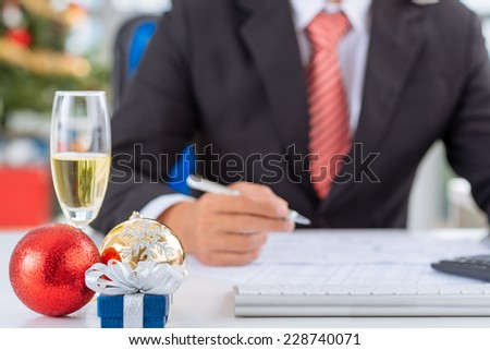 Christmas decorations and champagne flute on the table of businessman, selective focus - stock photo