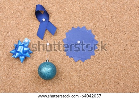 Christmas decorations and wrappings pinned to a cork notice board