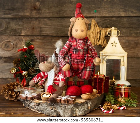 Christmas decorations. Elks, lantern, gingerbread cookies, walnuts, Christmas bell, fir tree  branch, cone and Christmas star against old wooden background