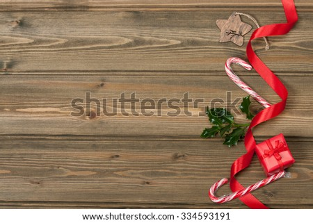 Christmas Decorations. Gift Box. Holy Leaf. Candy Cane. Space for Text. Wooden Background. - stock photo