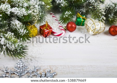 Christmas decorations, gifts and fir branches in the snow on a wooden table. Christmas border closeup.