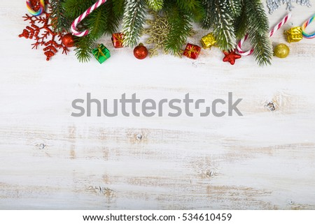 Christmas decorations, gifts and fir branches on a wooden table. Christmas border closeup.