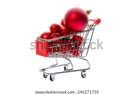 Christmas decorations: group of red Christmas balls in a shopping cart, Christmas tree decorations, isolated on white background - stock photo