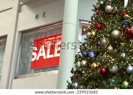 """Christmas decorations hanging in front of a partially hidden """"Sale"""" sign during the most lucrative season of the year for retail sales. - stock photo"""