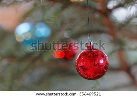 Christmas decorations hanging on a christmas tree branch.  Colorful red, and blue balls. Short depth of focus - stock photo